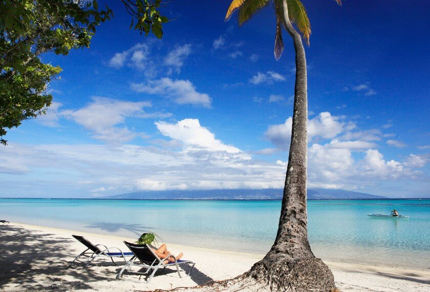 Woman relaxing on a sunchair at the beach of the hotel Sofitel Moorea Ia Ora Beach Resort